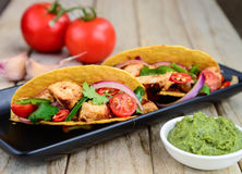 Chicken taco with mint chutney. Mexican taco with a filling of cherry tomatoes,chicken, cucumbers, salsa and onions and mint chutney Stock Photo