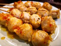 Chicken tendon meatballs plug into wooden stick and then grill. stock image