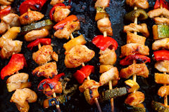 Chicken teriyaki kebabs with vegetables on black baking Stock Photos