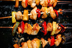 Chicken teriyaki kebabs with vegetables on black baking Stock Photography