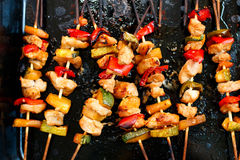 Chicken teriyaki kebabs with vegetables on black baking. Chicken teriyaki (doriyaki) kebabs with vegetables on black baking, tasty food Royalty Free Stock Photos