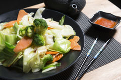 Chicken Teriyaki with steamed vegetables on a black plate royalty free stock photos