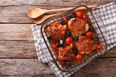 Chicken thigh baked with tomatoes and porcini mushrooms close up. In baking dish on the table. Horizontal view from above Stock Photo