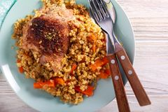 Chicken thigh with bulgur and carrot. On plate royalty free stock photography