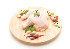 Chicken thigh. On wood board with black peppers ,garlics and dried chilli royalty free stock photography