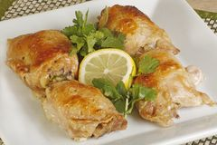 Chicken thighs. Four roast chicken thighs with coriander and lemon on a white plate Royalty Free Stock Photos