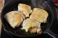 Chicken Frying in a skillet. Chicken thighs frying in a cast iron skillet Royalty Free Stock Images