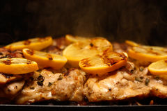 Chicken thighs on the Grill topped with lemons Royalty Free Stock Photo