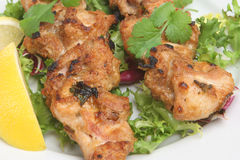 Chicken Tikka Kebabs. Indian chicken tikka kebabs with lettuce and lemon Royalty Free Stock Photos