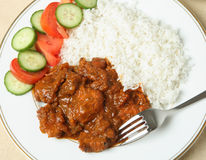 Chicken tikka masala. A plate of chicken tikka masala with basmati rice and a salad of cucumber and tomato Stock Photography