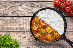 Chicken tikka masala Asian traditional spicy meat food and rice. In cast iron skillet with tomatoes, butter and parsley on vintage wooden background Stock Images