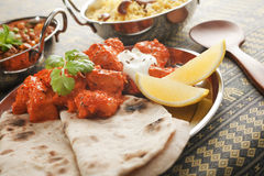 Chicken Tikka Masala with Chapati and Rice Pilau. Chicken tikka masala, Britain's favoutite dish, garnished with lemon, coriander and yoghurt,  and with chapatis Stock Photos
