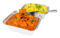 Chicken Tikka Masala Curry And Pilau Rice In Foil Take Away Trays. Creamy chicken tikka masala curry and pilau rice in foil take away containers isolated on a Stock Photo