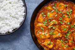 Chicken tikka masala national Indian spicy meat food with butter. And rice in cast iron skillet Royalty Free Stock Images