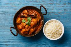 Chicken tikka masala spicy curry meat food. And basmati rice on blue wooden background stock photos