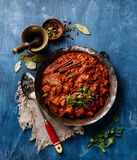 Chicken tikka masala spicy curry meat food. In copper pan on blue wooden background Royalty Free Stock Photos