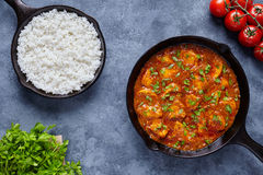Chicken tikka masala traditional Asian spicy butter meat food. With tomatoes, parsley and rice in cast iron skillet Stock Photography