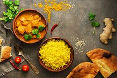 Chicken tikka masala with yellow rice and naan on a dark brown background. Indian food. Top view, copy space, flat lay