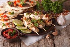 Chicken tikka on skewers, flat bread and chutney closeup. horizo Royalty Free Stock Photos