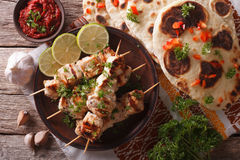 Chicken tikka on skewers, naan flat bread closeup. horizontal to Royalty Free Stock Photography