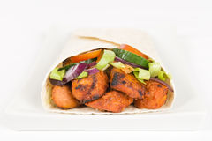 Chicken Tikka Wrap. BBQ Tandoori chicken tikka with salad wrapped in a flatbread on a white background royalty free stock photo
