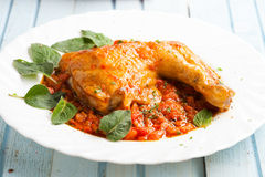 Chicken in tomato sauce and fresh herbs Stock Photo
