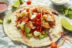 Chicken Tortilla wraps with fresh vegetable mix, avocado, lime, greek yogurt and sweet chilli sauce.  stock image
