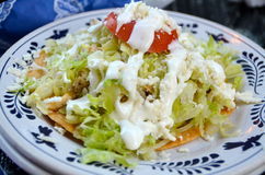 Chicken tostada with sour cream. A Mexican food classic: chicken tostada with lettuce, sour cream, cheese, and tomato on a crispy tortilla Stock Images