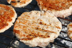 Chicken or turkey burgers for hamburger on grill. Chicken or turkey poultry meat barbecue grilled burgers for hamburger prepared on bbq smoke grill, close up Royalty Free Stock Image
