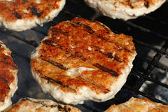 Chicken or turkey burgers for hamburger on grill. Chicken or turkey poultry meat barbecue grilled burgers for hamburger prepared on bbq smoke grill, close up Royalty Free Stock Photos