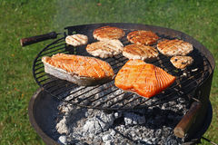 Chicken or turkey burgers and salmon fish on grill Stock Photography