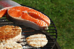 Chicken or turkey burgers and salmon fish on grill. Chicken or turkey poultry meat barbecue grilled burgers for hamburger and salmon fish fillet steak prepared royalty free stock photos