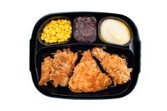 Chicken TV dinner in plastic tray. A cooked TV dinner of fried chicken, corn, mashed potatoes and dessert in a plastic black tray Royalty Free Stock Photography
