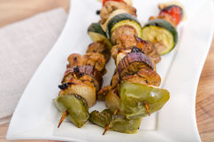 Chicken and vegetable kabobs on white plate Royalty Free Stock Image
