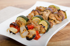 Chicken and vegetable kabobs on white plate Royalty Free Stock Photo