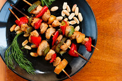 Chicken and vegetable kebabs on black plate. On wooden table Royalty Free Stock Photography