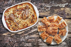 Chicken Vegetable Stew In Baking Pan And Plateful Of Traditional Gibanica Crumpled Cheese Pie Slices On Old Weathered Picnic Table. Oven baked Vegetable Stew Royalty Free Stock Image
