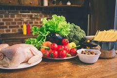 Chicken, vegetables, fruit, on the table in the kitchen. royalty free stock photos