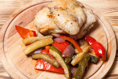 Chicken with vegetables served on round cutting board on burned Royalty Free Stock Photo
