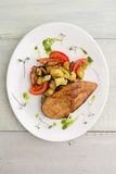 Chicken with vegetables: zucchini, mushrooms. Piece of fried chicken with vegetables: zucchini, tomatoes, mushrooms with pesto and herbs, served on a white plate Royalty Free Stock Photo