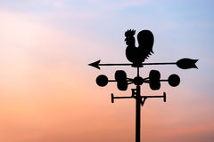 Chicken wind vane with compass and sky.  stock image