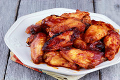 Chicken wings. Plate of delicious barbecue chicken wings with shallow depth of field on a rustic background Stock Photos