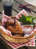 Chicken wings. Grilled chicken wings with tomato sauce in basket, selective focus Royalty Free Stock Image