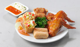 Chicken wings. Fried chicken wings accompanied with assorted fried spring rolls and dumplings Stock Photo
