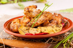 Chicken wings with baked potatoes Stock Images