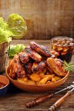 Chicken wings with baked potatoes and cold drink stock photo