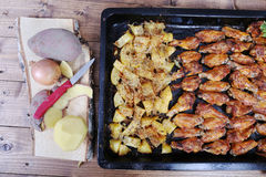 Chicken wings with baked potatoes Royalty Free Stock Photos