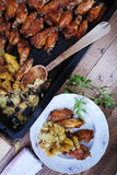 Chicken wings with baked potatoes Royalty Free Stock Photography