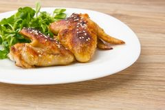Fried chicken wings. Chicken wings of a barbecue on a white plate with salad. Chicken wings of a barbecue on a white plate with salad Stock Photos