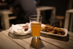 Chicken wings, beer, sauces on the table in the pub. Looking nice Stock Photography